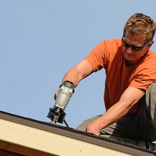 A Roofer Nails in Shingles