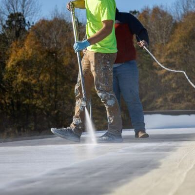 Roofers Spray on a Roof Restoration Coating.