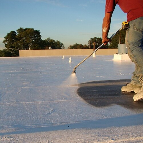 A Roofer Sprays a Silicone Roof Coating.